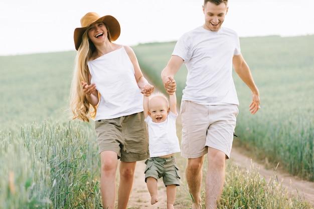 Молодая семья развлекается со своим маленьким ребенком в поле