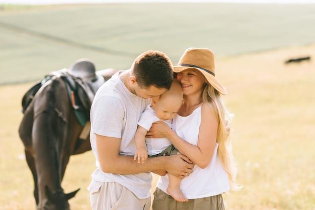 Молодая семья весело провести время в поле. родители и ребенок с лошадью