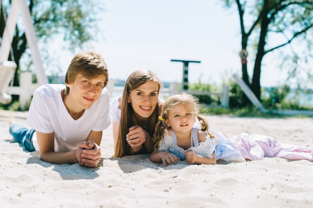 屋外で一緒に時間を過ごす幸せな家族。父、母と娘は楽しんで、ビーチで遊んで