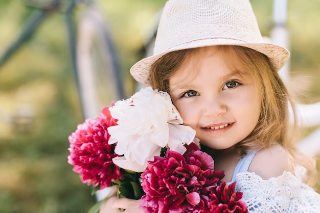 緑の背景の花の大きな花束と笑みを浮かべて少女の肖像画