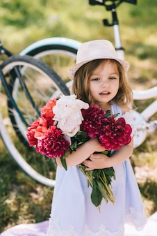 Портрет маленькой улыбающейся девушки с большим букетом цветов на зеленом фоне