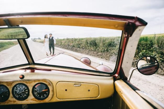 レトロな車の近くのフィールドの道を歩いてスタイリッシュな結婚式のカップル。フロントガラス車の眺め。