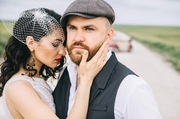 レトロな車の近くのフィールドの道を歩いてスタイリッシュな結婚式のカップル。