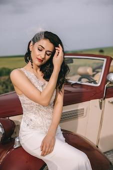 フィールドの道で赤いレトロな車に座っているスタイリッシュなかわいい花嫁