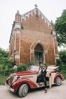 レトロな車で教会の近くのスタイリッシュな結婚式のカップル。