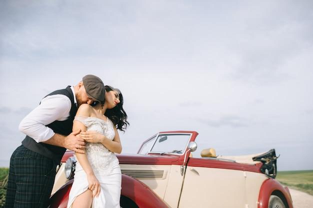 レトロな車の近くの野外道路でスタイリッシュな結婚式のカップル。