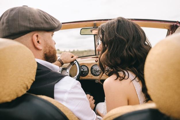 スタイリッシュな結婚式のカップルがレトロな車でキス