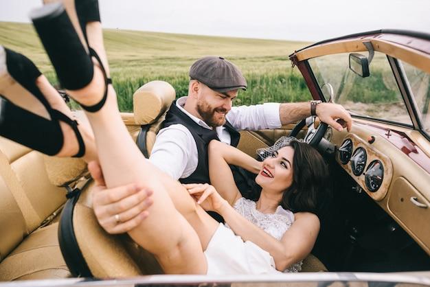 レトロな車で抱き締めるスタイリッシュな結婚式のカップル