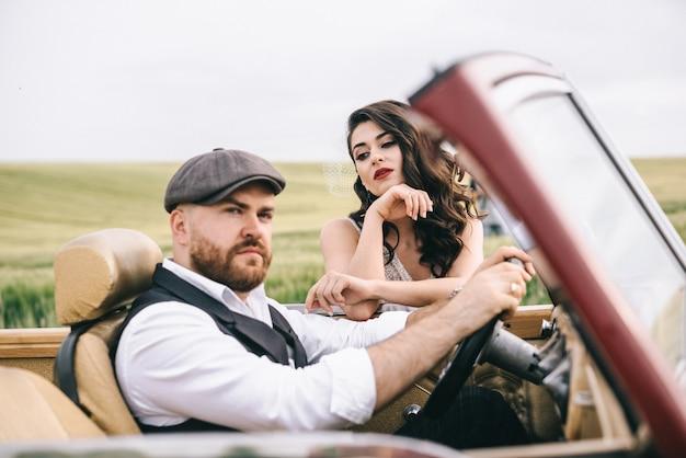 レトロな車の近くの緑のフィールドでスタイリッシュな結婚式のカップル。