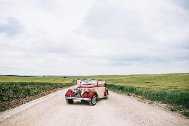 フィールドの道でスタイリッシュな赤いレトロな車