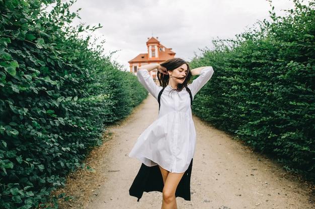 赤い宮殿の背景に緑の路地を歩いている若い白人のスタイリッシュな女の子