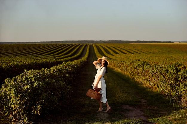 スグリ畑の前でフルーツバスケットを保持している女性。