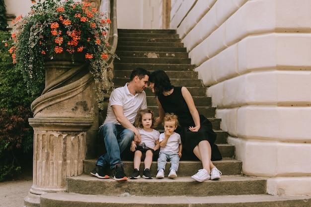Красивый молодой отец и красивая мама в солнечной летней природе играют со своими милыми маленькими детьми