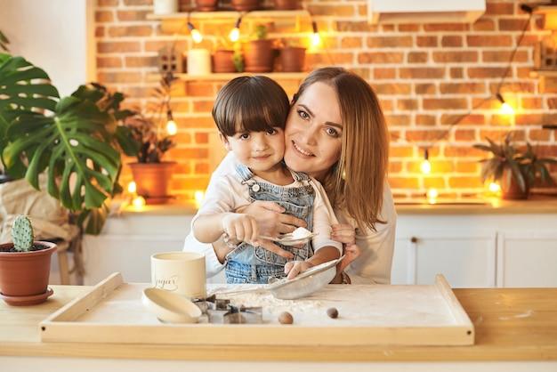若い美しい家族楽しんで、日当たりの良いキッチンで調理