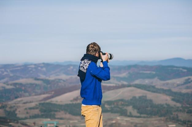 下の山々を見下ろす崖の端にあるカメラを持つ男