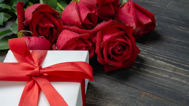赤いバラの花と暗い木製のテーブルに白いプレゼントボックスの花束。