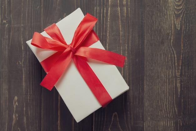 Белая присутствующая коробка на темном деревянном столе. с днем рождения