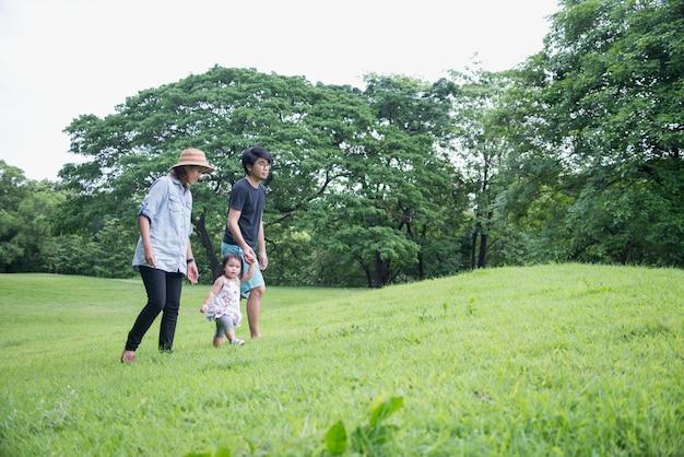 Группа в составе азиатская семья с маленькими детьми гуляя вдоль поля зеленой травы в парке в лете.