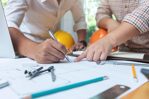エンジニアアーキテクトと不動産エージェントのオフィスチームが設計図を作成