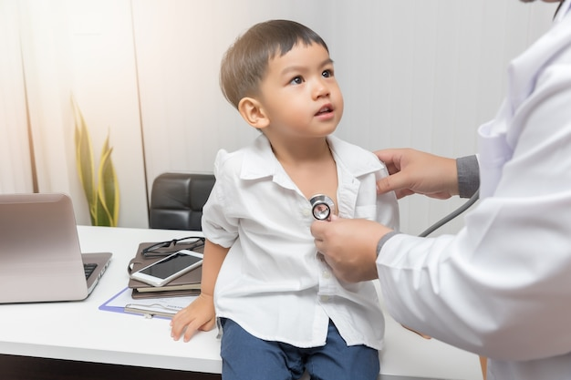 Педиатрический врач осматривает маленького азиатского мальчика стетоскопом