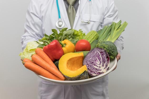 健康と栄養のコンセプト。医者は新鮮な果物や野菜のボウルを保持しています。