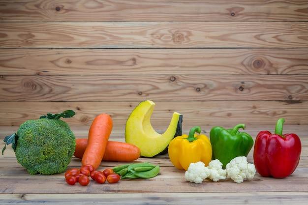 木製の背景に様々な新鮮な野菜。