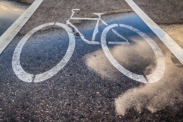 ぬれた自転車レーンと雲の反射