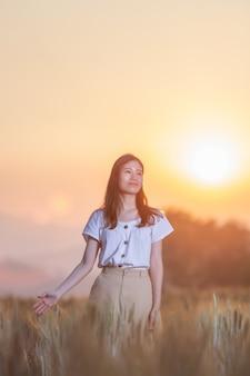 日没時に麦畑で楽しんでいる女性