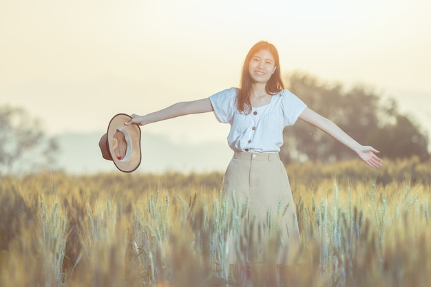 夏の麦畑で楽しんでいる女性