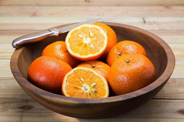 ナイフで木製のテーブルの上のオレンジ色の果物