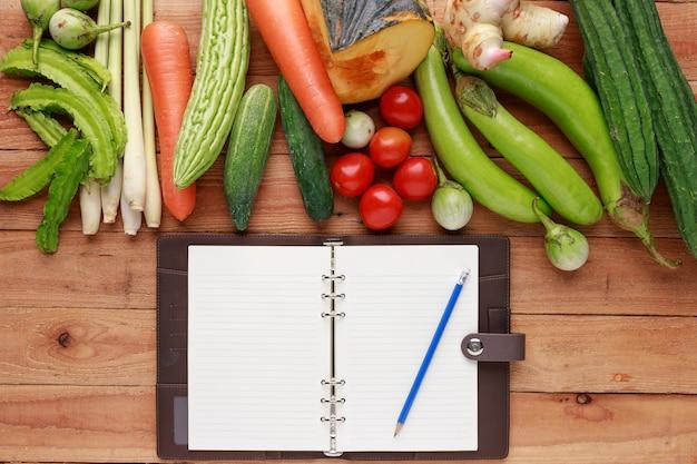 空白のノートブックと木製の背景に鉛筆で様々な野菜。上面図