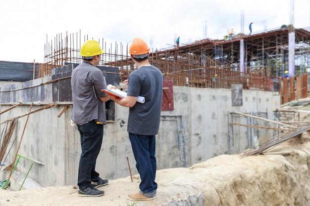 Инженер и архитектор работают на строительной площадке