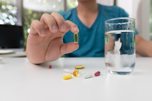 Молодой человек, держащий в руке таблетки фармацевтической медицины