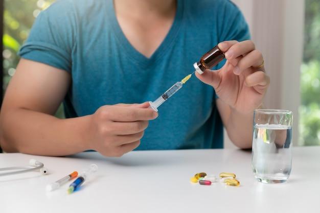 Молодой человек, держащий в руке иглы для инъекций и вакцины