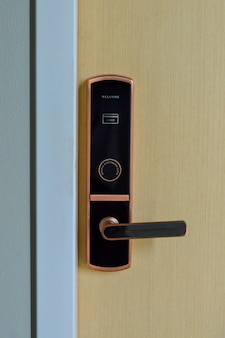 キーカードを使用したデジタル電子ドア。セキュリティと部屋へのアクセスのために木製のドアに取り付けられたデジタルドアロック