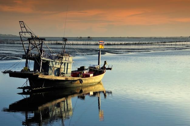 夕焼けの空の環境と漁師のボート