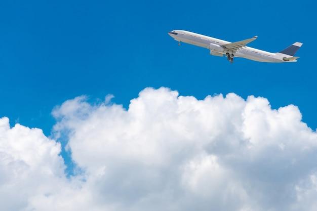 明るい青空と白い雲の上を飛ぶ商用飛行機。