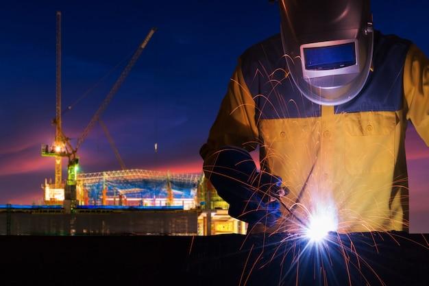 Промышленный рабочий сваривает стальную конструкцию для проекта строительства инфраструктуры
