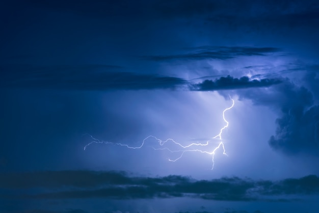 Удар молнии грозы на темном фоне облачного неба ночью.