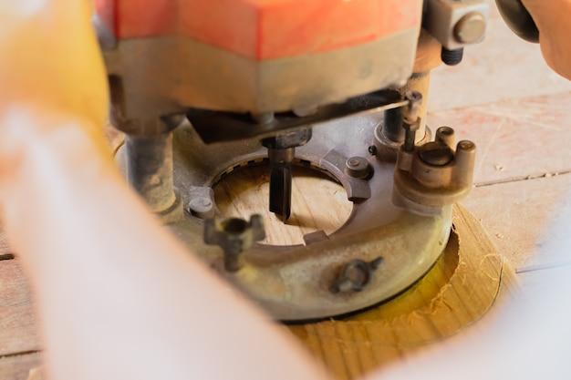 木製の厚板の床に作業ルータのマシンを使用して人々の手