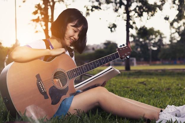 素敵なアジアの十代の女の子が自由時間でリラックスしてギターを弾いています。