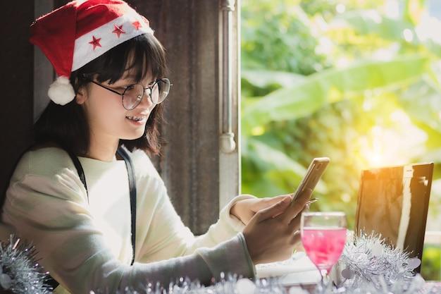 クローズアップアジアの女性、十代の少女はスマートフォンを使って幸せにクリスマスの帽子を着る