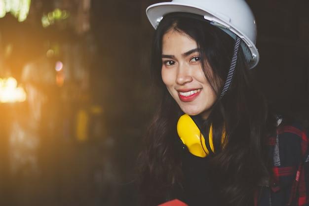 アジアの女性が工場で働く、業界のポーズ