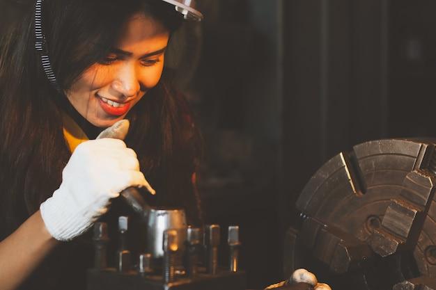 アジアの女性が幸せな機械を使用して、工場で働いています。
