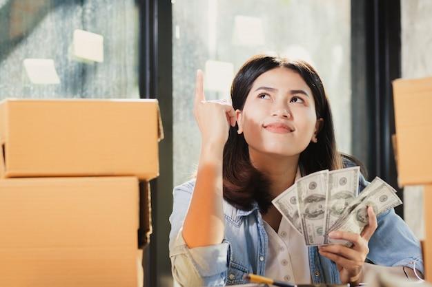 ドル紙幣のお金を保持しているアジアの女性は幸せと笑顔します。