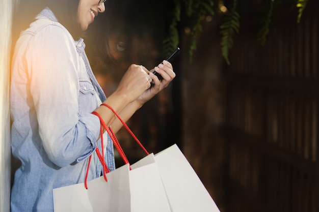 女性の幸せと自由時間で働くスマートフォンを使用して。