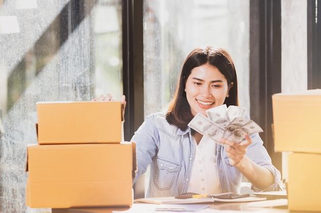 Женщина, держащая деньги банкноты улыбки с счастливым.