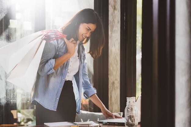 アジアの女性が働いて、幸せと一緒に買い物にラップトップコンピューターを使用して。
