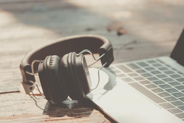 ラップトップコンピューターと背景のテーブルの上のヘッドフォン。