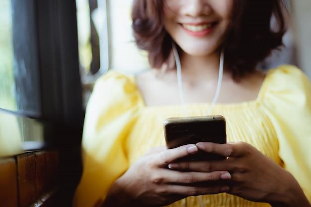 Женщина с помощью смартфона, слушать музыку в свободное время с счастливым.
